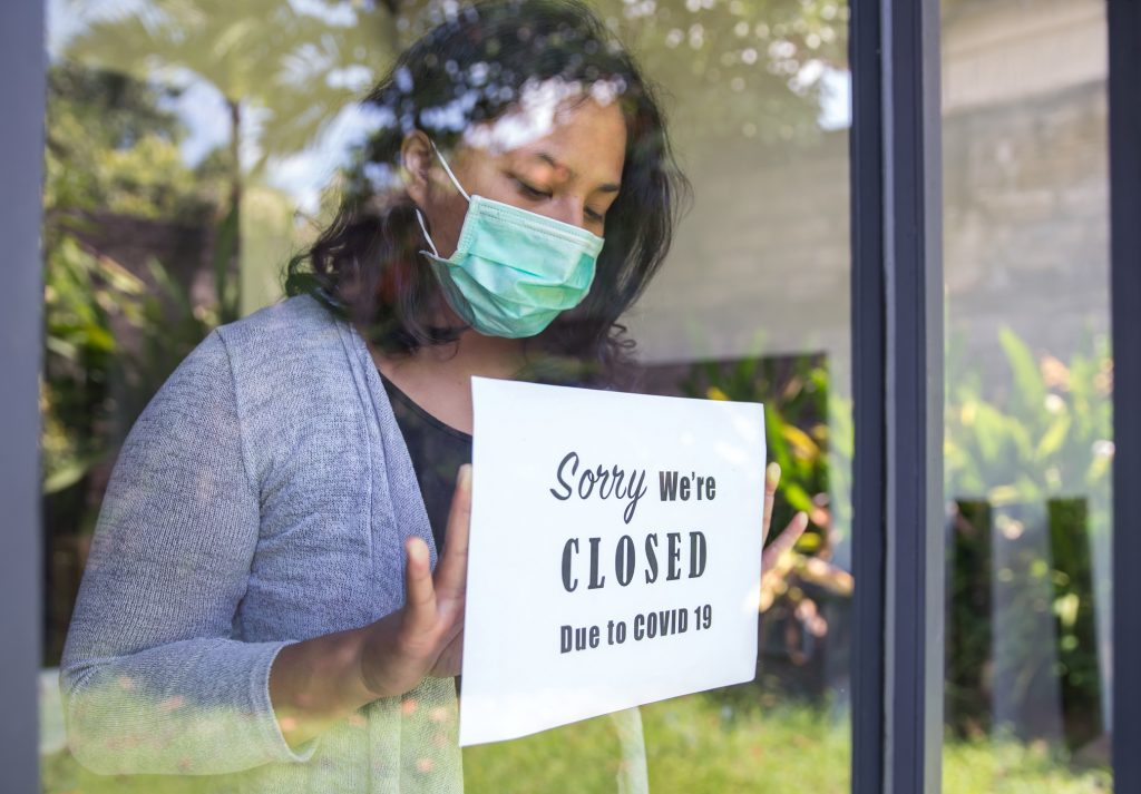 """Woman in mask posting a sign in a store window that reads """"Sorry we're closed due to COVID-19"""""""