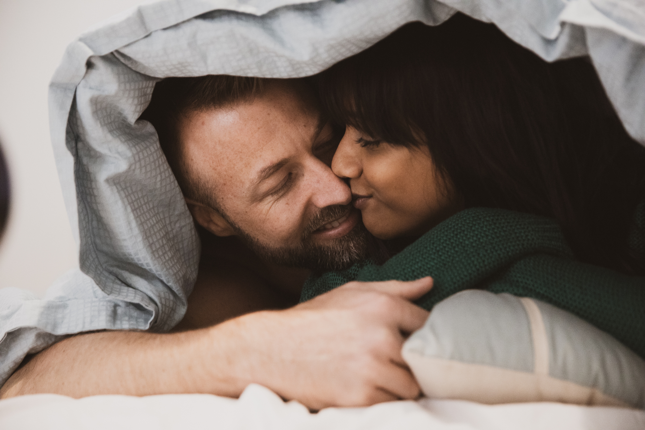 An interracial couple smiling and kissing under bedsheet covers