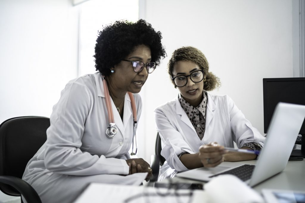Two Black female physicians consult a computer screen together
