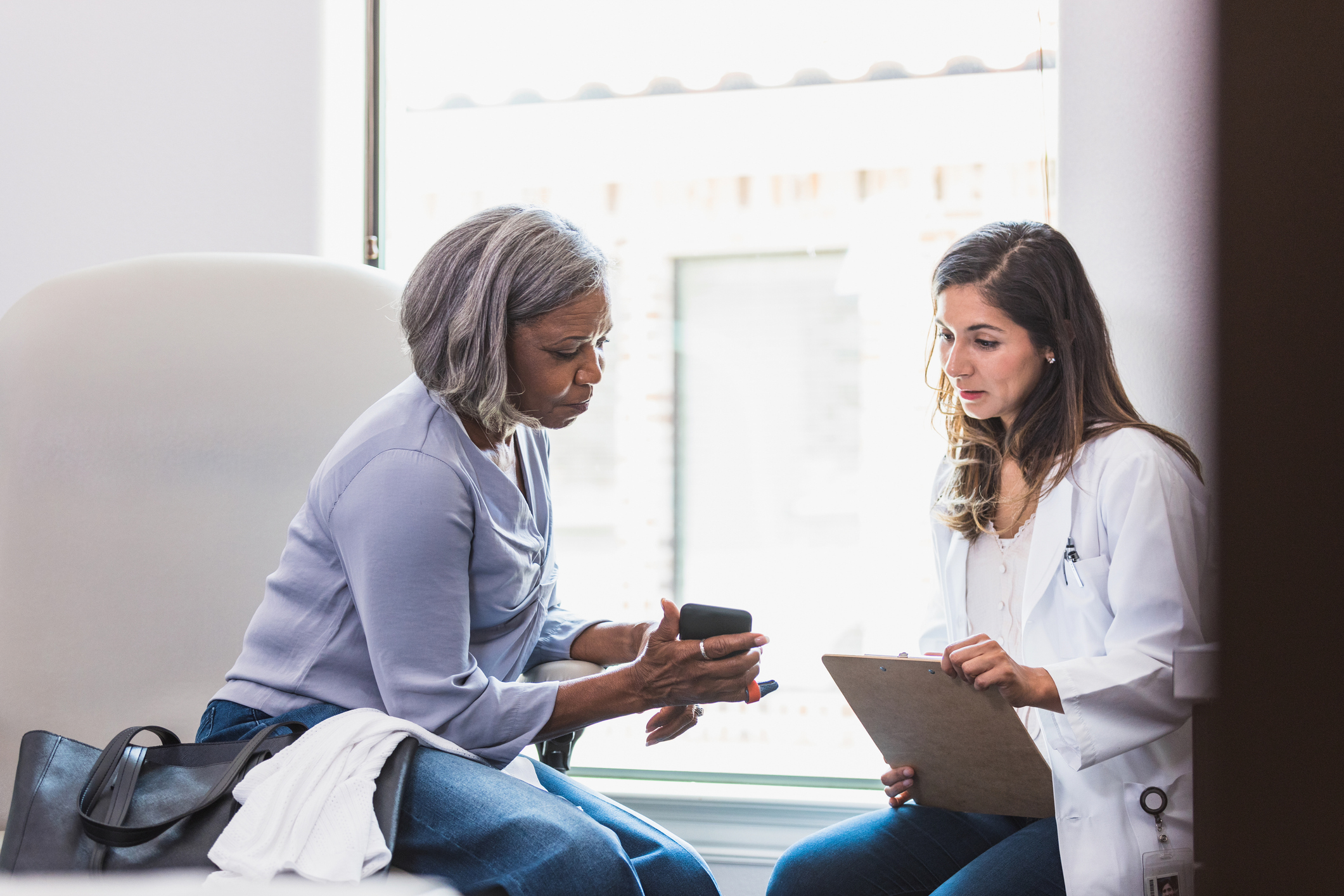 A senior woman shows a female doctor a health log she has been keeping on her smartphone