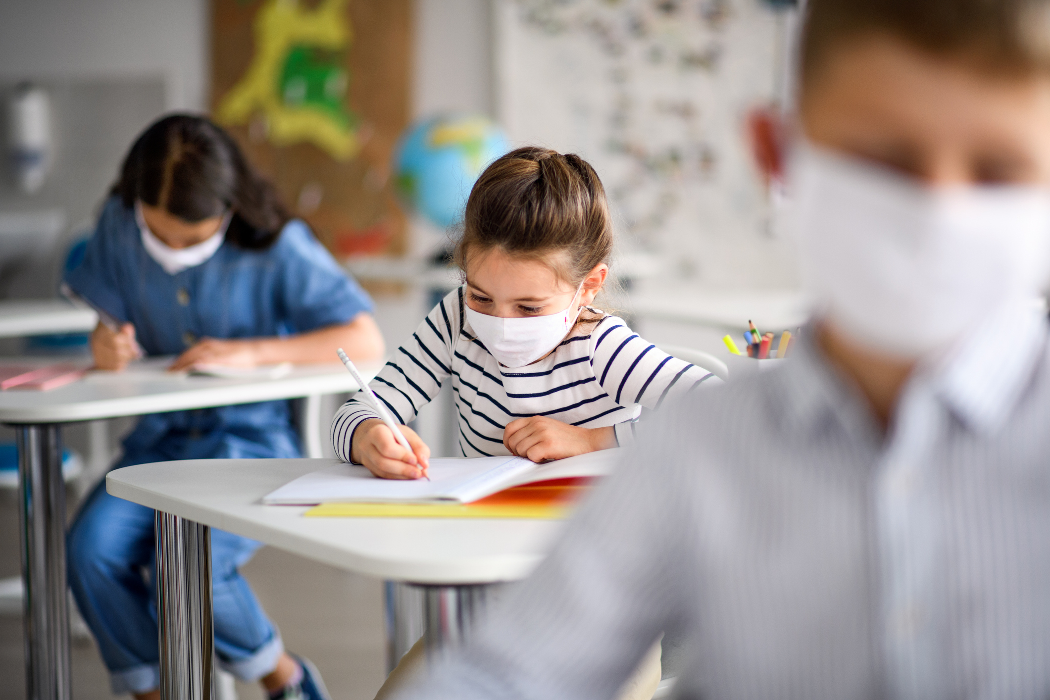 Children wearing face masks study at their desks in a classroom