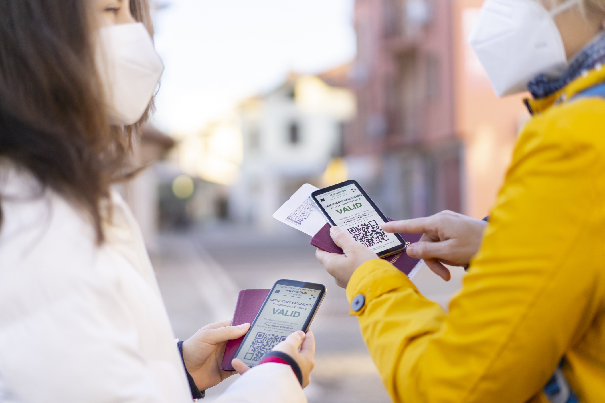 Two women in masks holding passports check digital vaccination certificates on their cellphones.