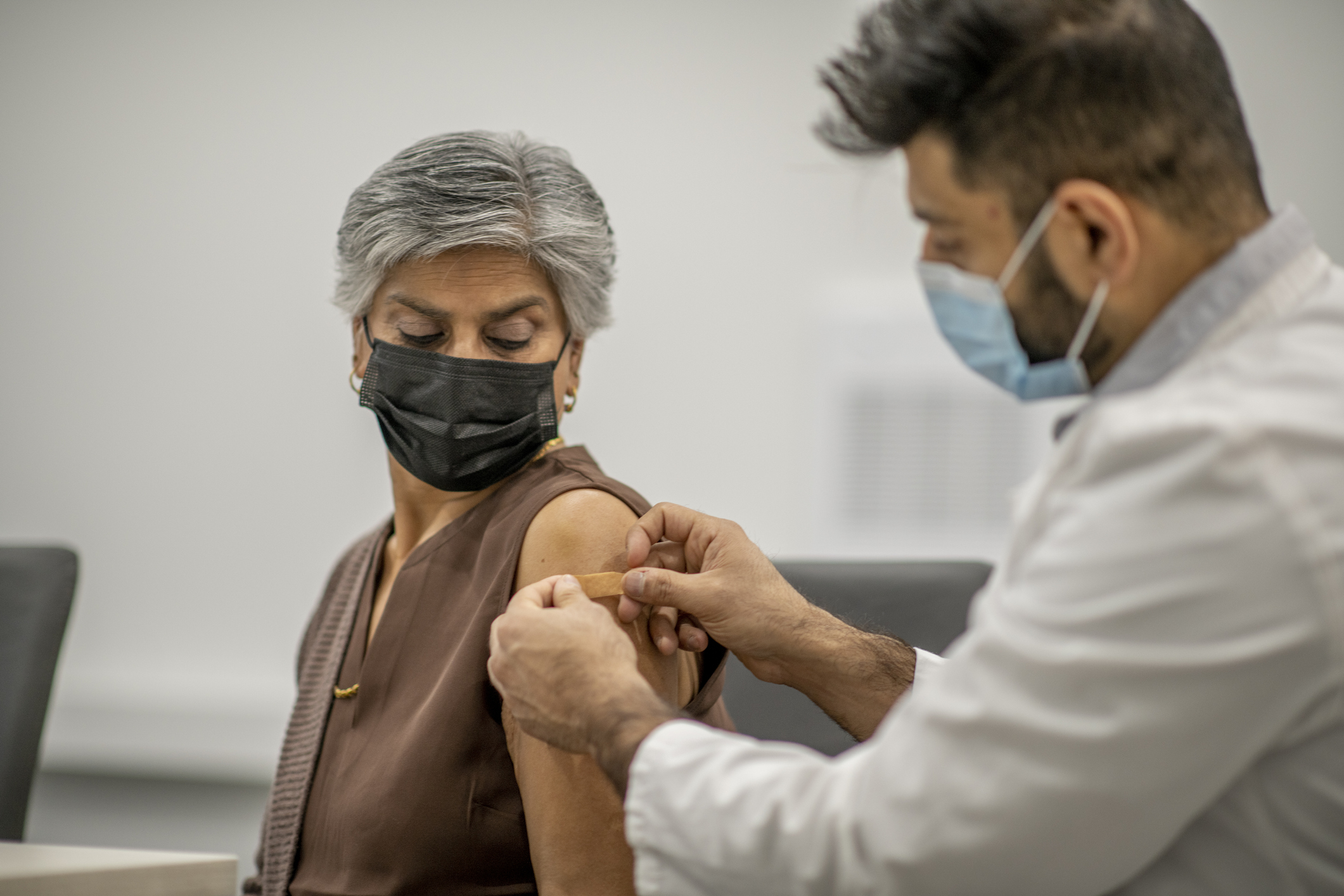 A male doctor puts a bandaid on an older woman's arm upper after administering a COVID-19 vaccine