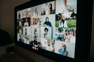 Close up of a computer screen displaying many people on a video call.
