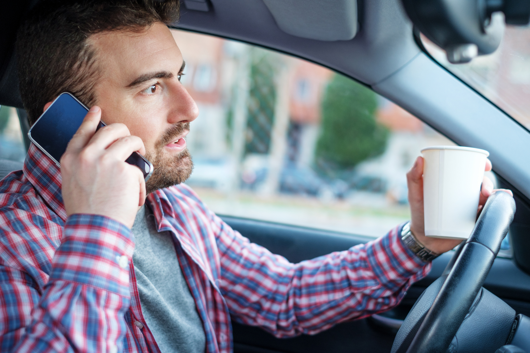 Distracted male driver holding a coffee cup