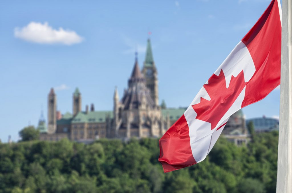 Closeup of Canadian flag waving with Canada's Parliament Hill in the background