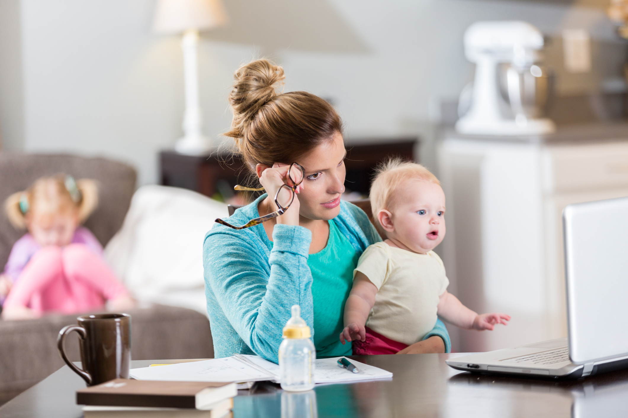 Tired Caucasian mother sitting at computer while taking care of two babies