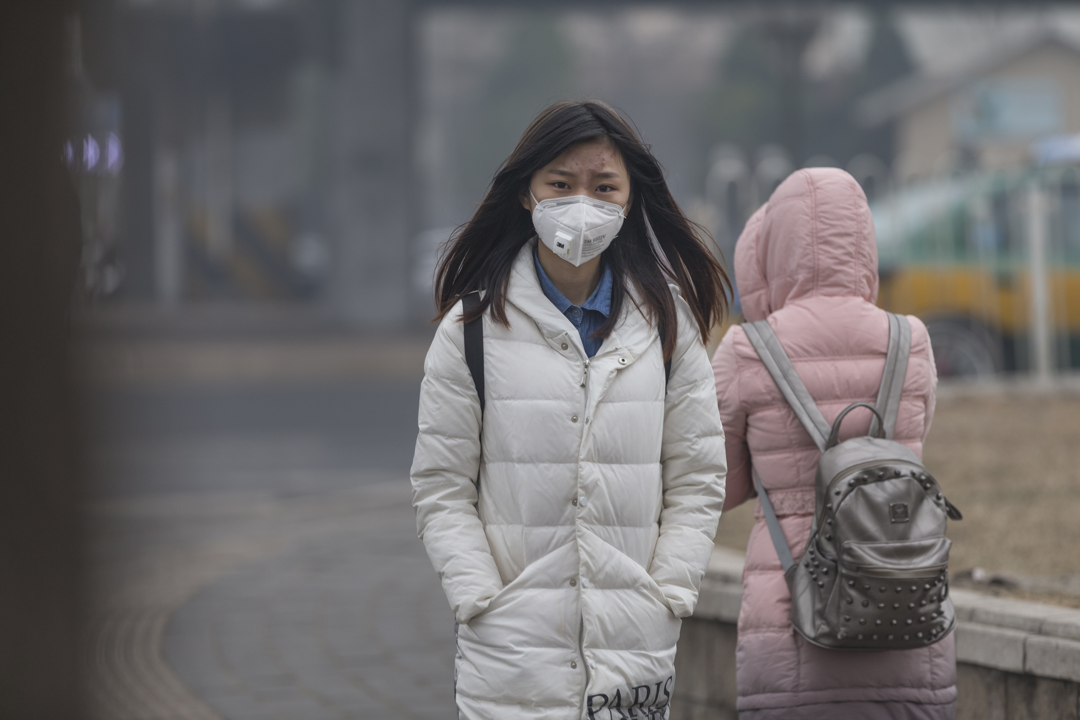 Young Asian woman walking outside in a city while wearing a face mask