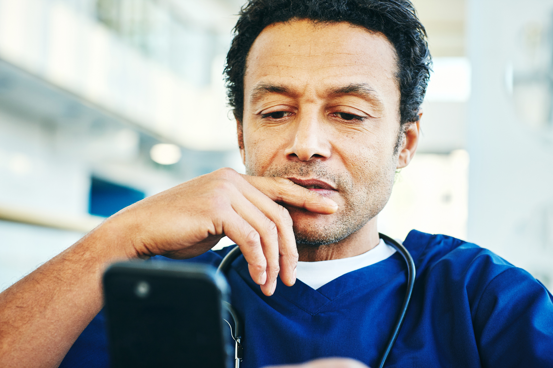 Male physician looking concerned at his smartphone