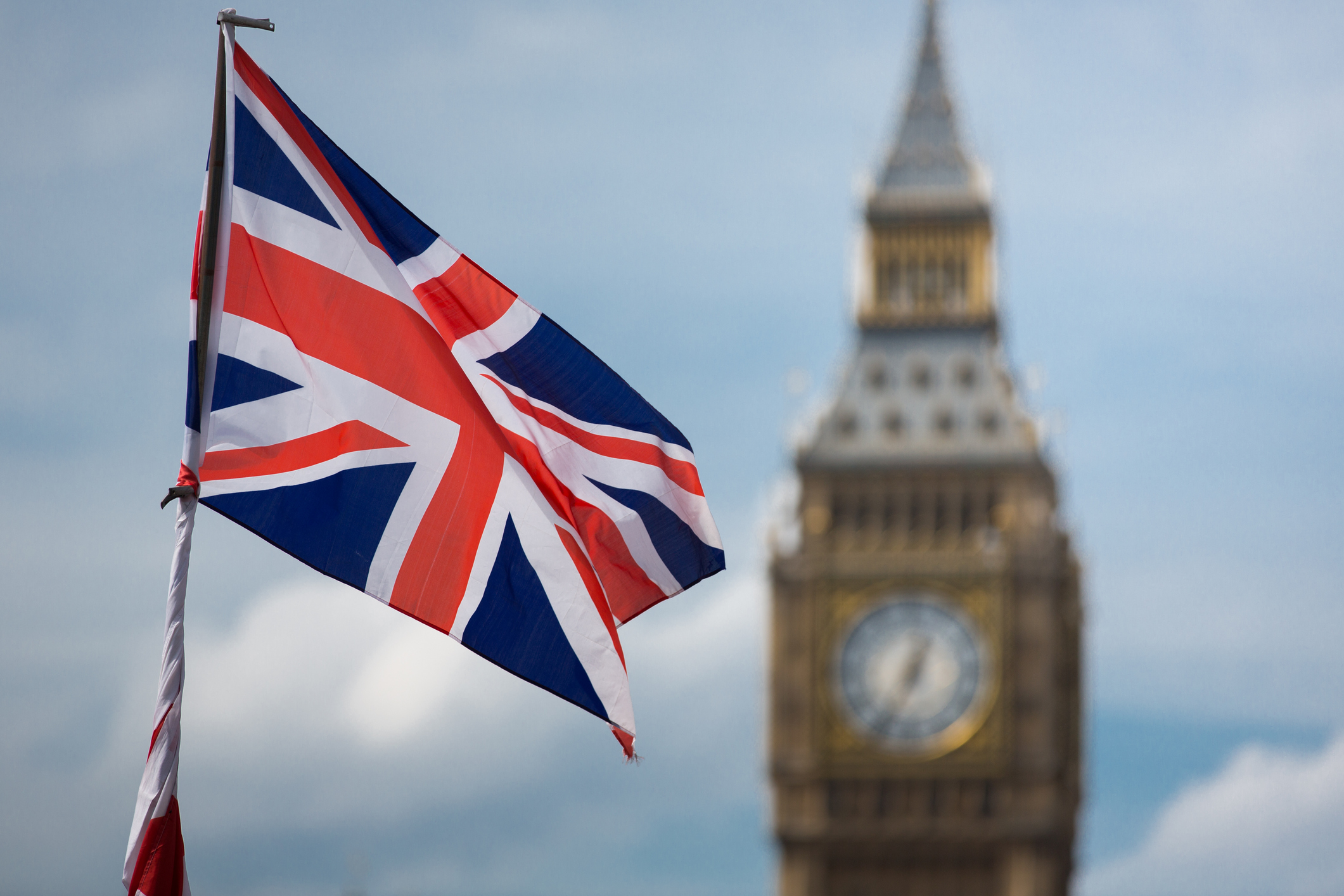 Closeup of a British Union Jack flag with Big Ben clock tower in the background