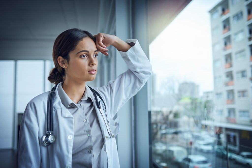 Young physician leaning against window and looking pensively outside a window