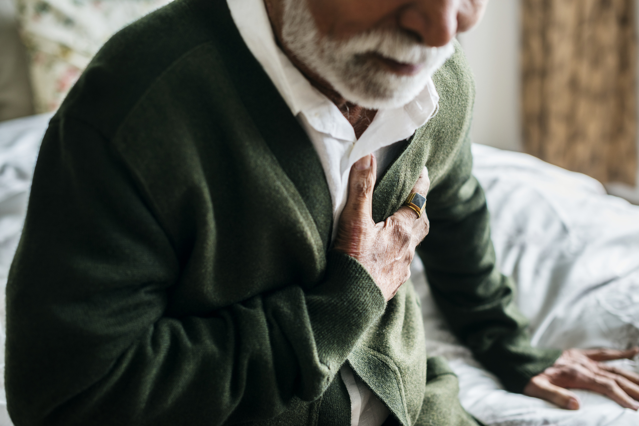 Elderly South Asian man clutching his chest in pain