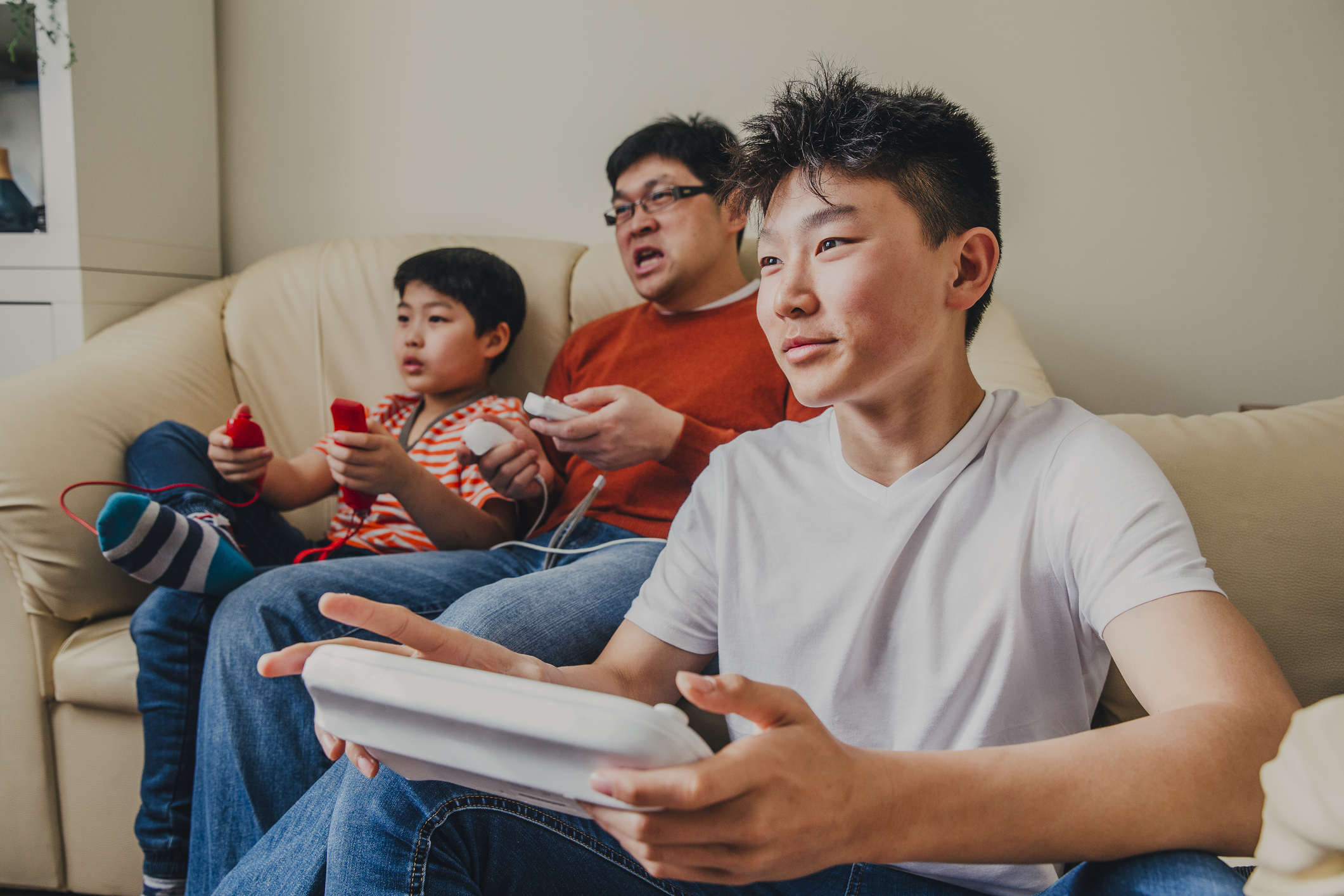 Asian boys and their father sitting on the couch and playing video games