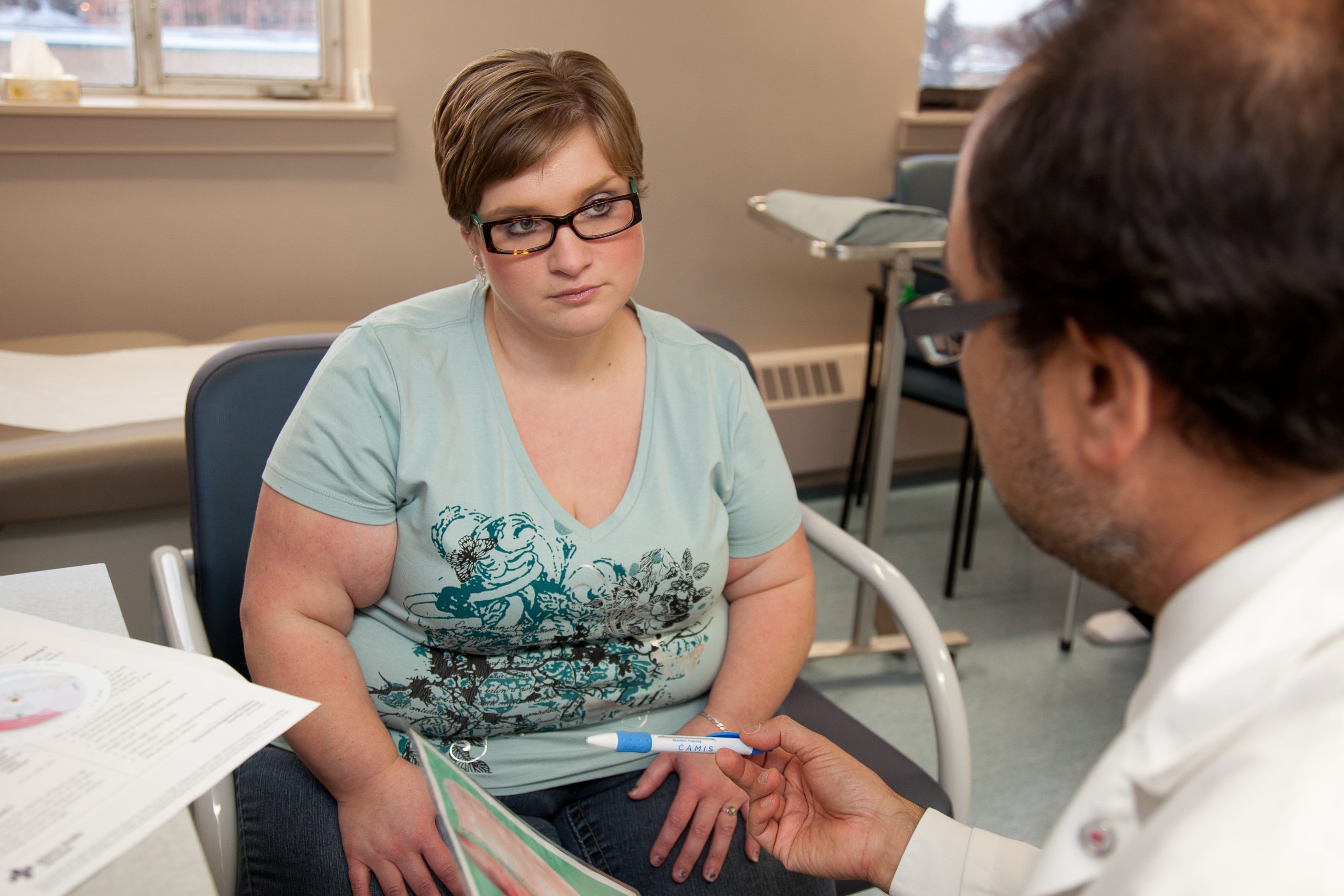 Seated female patient with obesity listens skeptically to a male physician