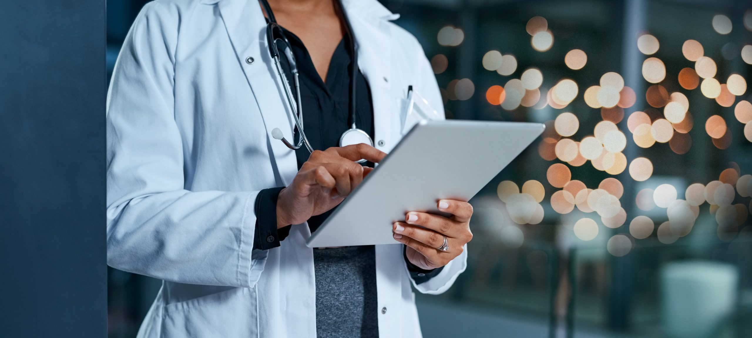 Female physician using a tablet in a hospital at night