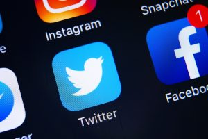 Closeup of Twitter and Facebook and other social media apps on a smartphone screen