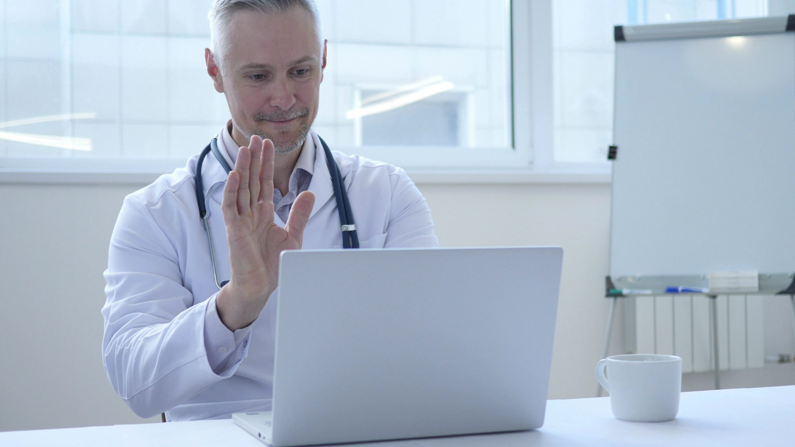 Male physician doing virtual health care and waving at his laptop screen