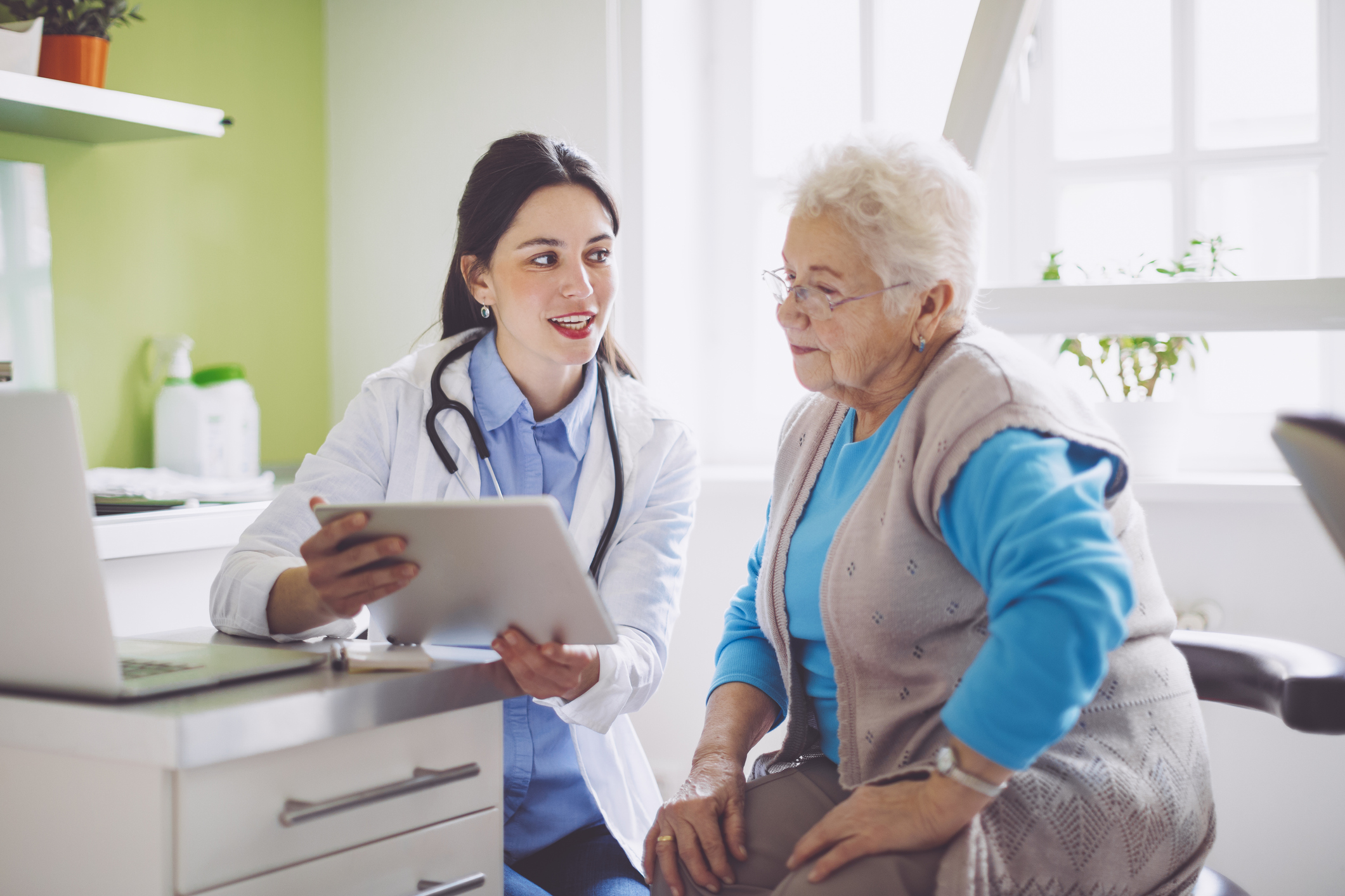 Female physician showing a tablet to older female patient