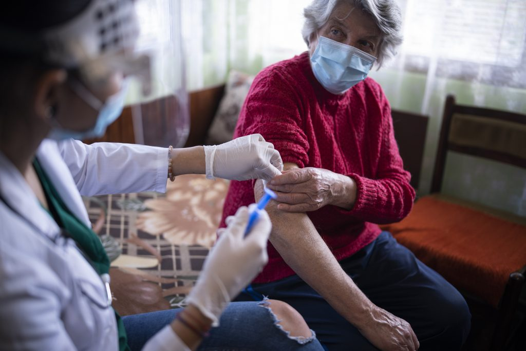 Health worker administering vaccine to senior woman at her home