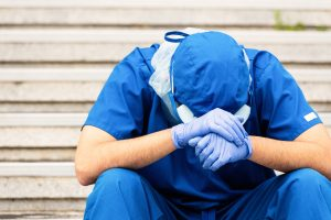 Overworked physician in scrubs sits on hospital steps with head in handss